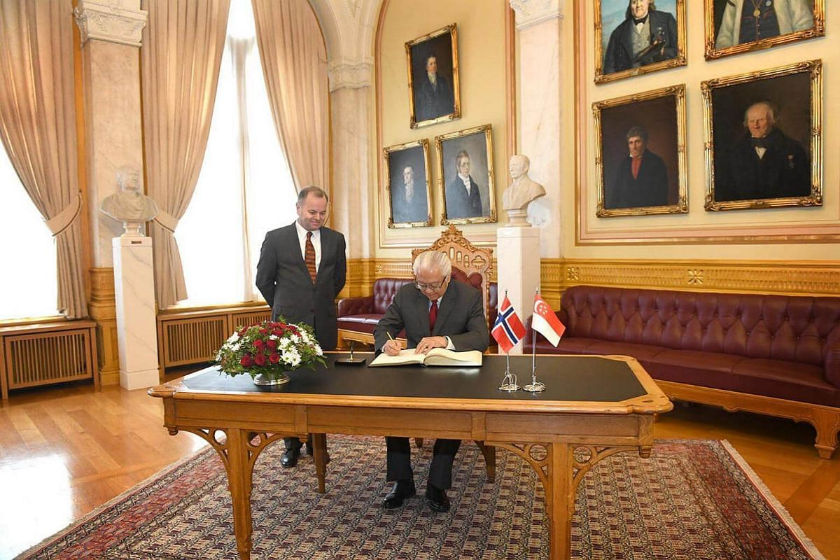 Tony Tan (centre) signs the guest book with Olemic Thommessen, president of the Storting looking on in Stortinget.