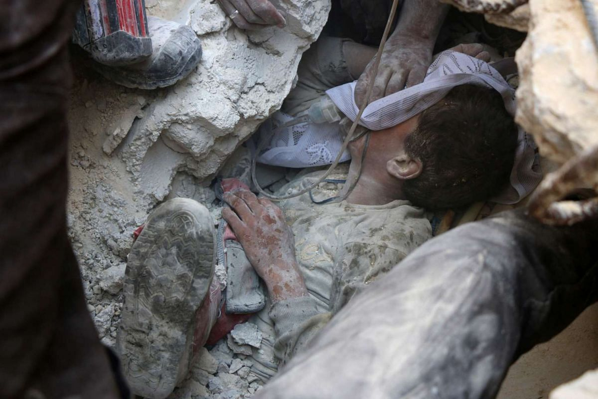 A young Syrian boy receives oxygen as he is pulled from the rubble of a building following Russian air strikes on the rebel-held Fardous neighbourhood of the northern embattled Syrian city of Aleppo on October 11, 2016.  PHOTO: AFP