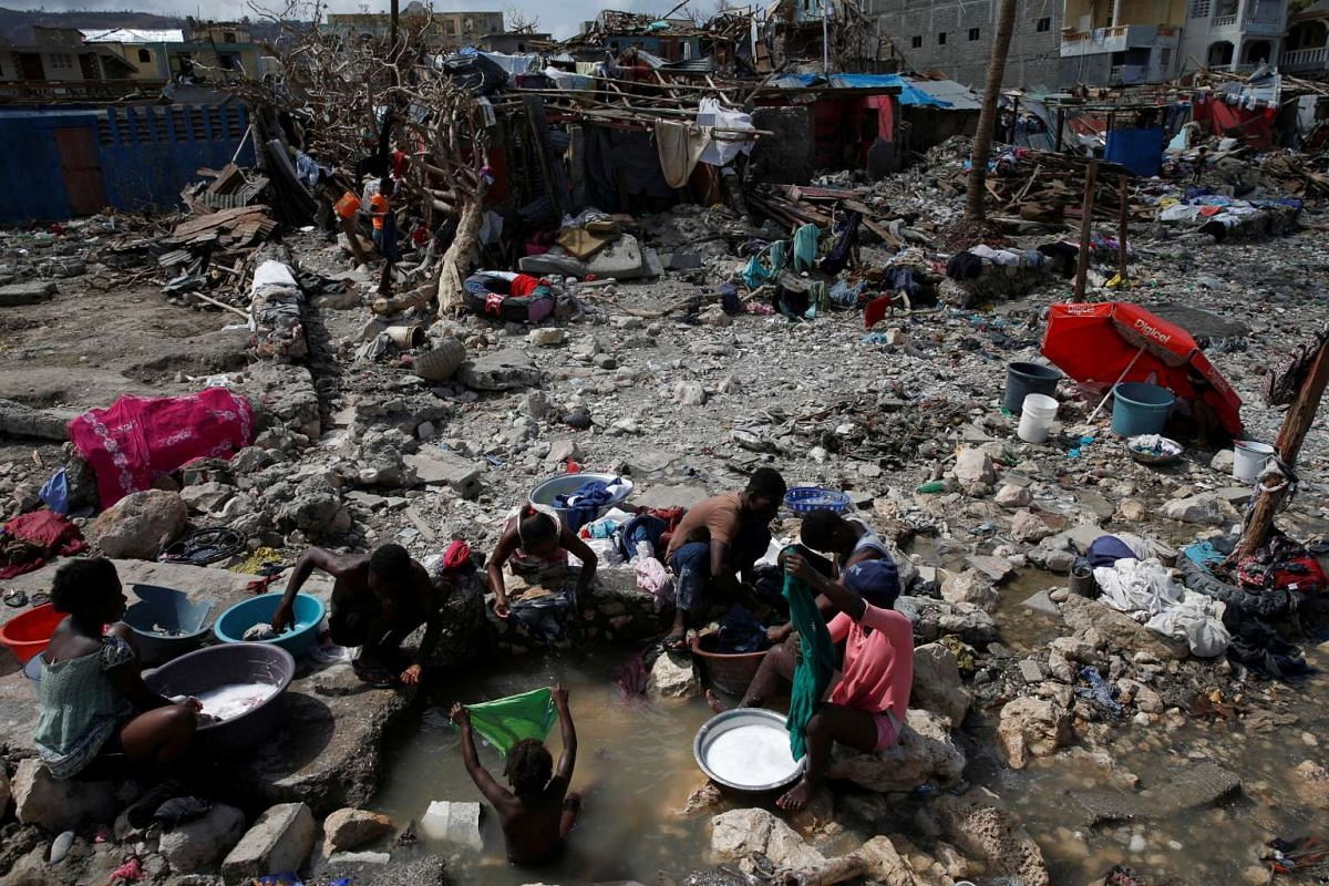 People wash their clothes on a beach near destroyed houses after Hurricane Matthew hit Jeremie, Haiti, October 10, 2016. PHOTO: REUTERS