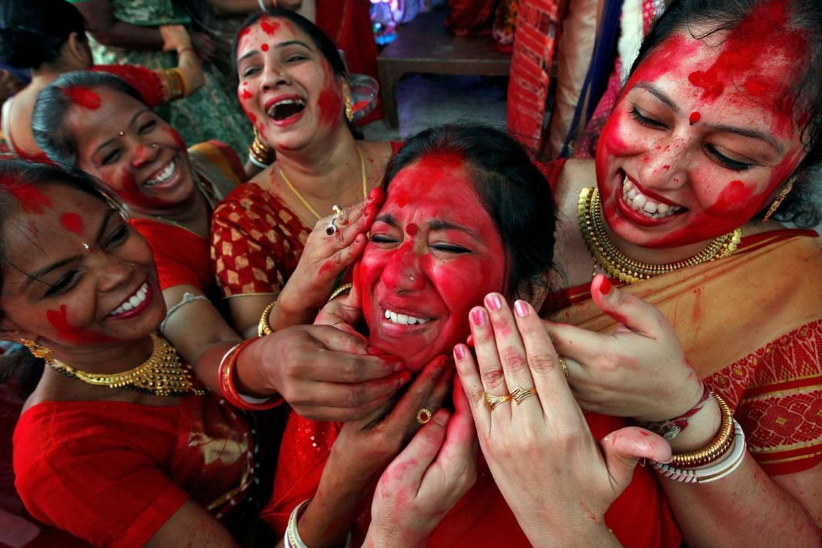 """Hindu women apply """"sindhur"""", or vermillion powder, on the face of a woman after worshipping the idol of the Hindu goddess Durga on the last day of the Durga Puja festival in Chandigarh, India October 11, 2016. PHOTO: REUTERS"""