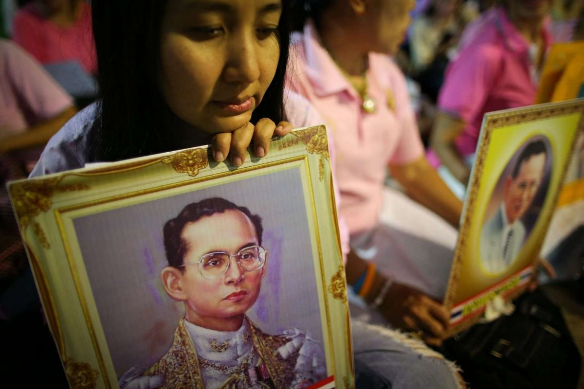 Thai well-wishers holding portraits of the monarch pray for a healthy recovery of Thai King Bhumibol Adulyadej at the Siriraj Hospital in Bangkok on Oct 12, 2016.