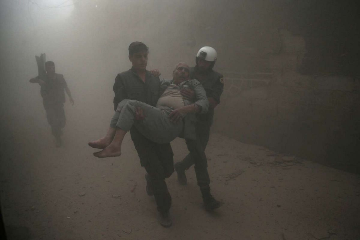 Civil defence members carry an injured man after an airstrike hit the rebel-held Douma neighbourhood of Damascus in Syria on Oct 12, 2016.