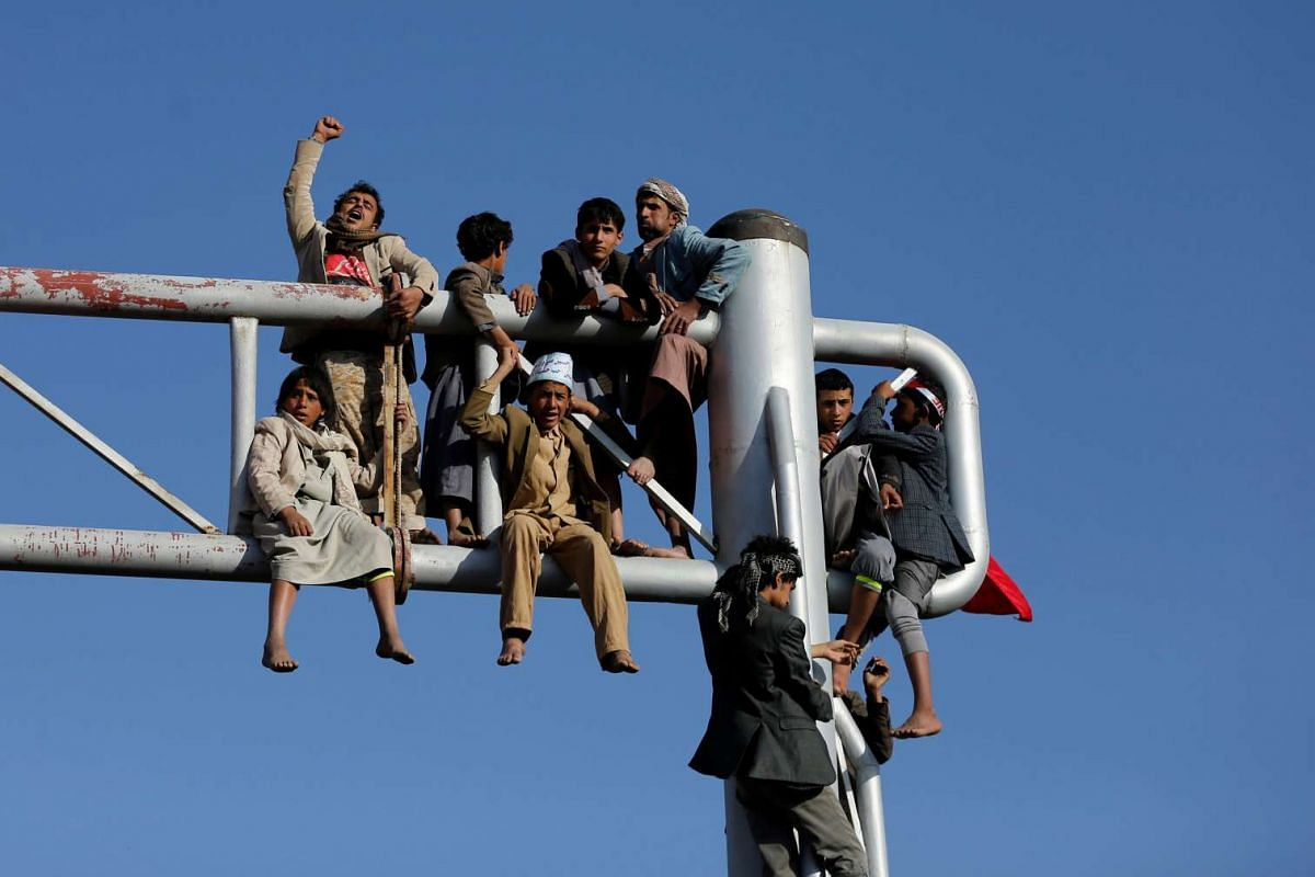 People climb a billboard during a demonstration to commemorate Ashura in Sanaa, Yemen, on Oct 12, 2016.