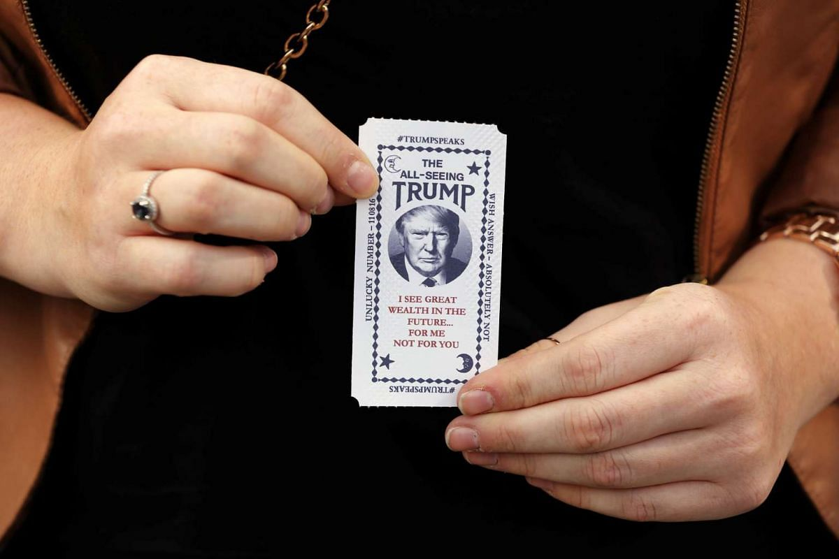 A woman holds a ticket dispensed from a Donald Trump-themed fortune-telling machine in Columbus Circle in New York, US, on Oct 12, 2016.