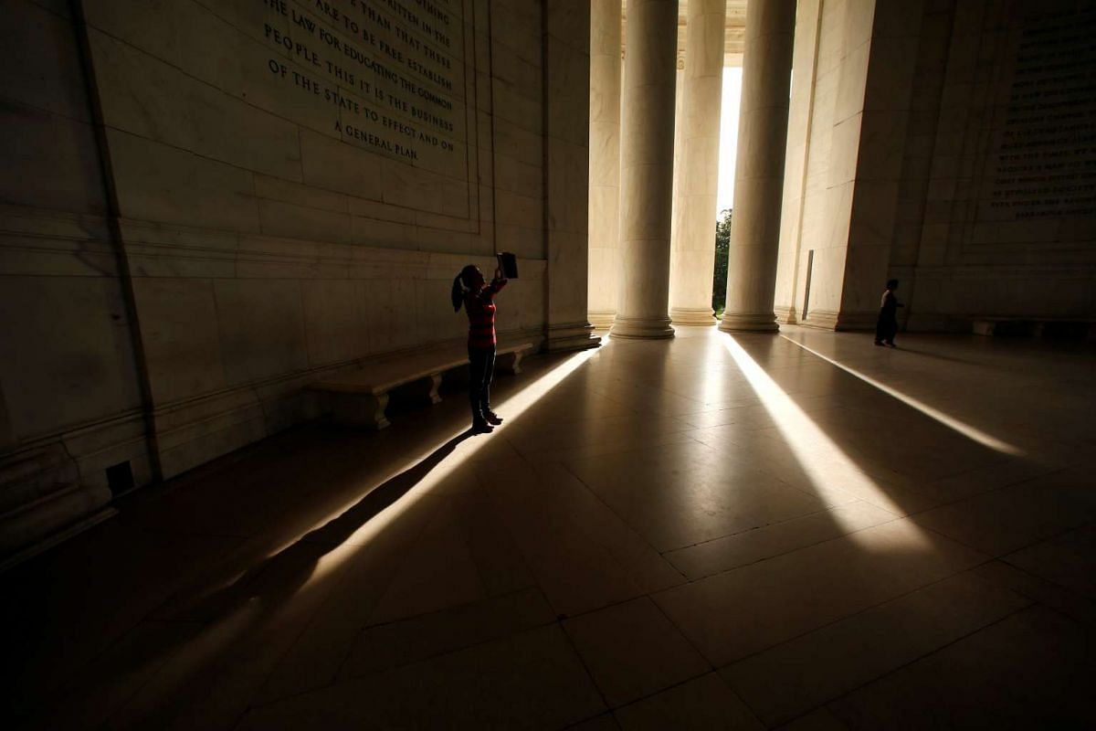 A visitor to the Jefferson Memorial in Washington holds up her tablet to take a photo of Jefferson's statue on Oct 12, 2016.