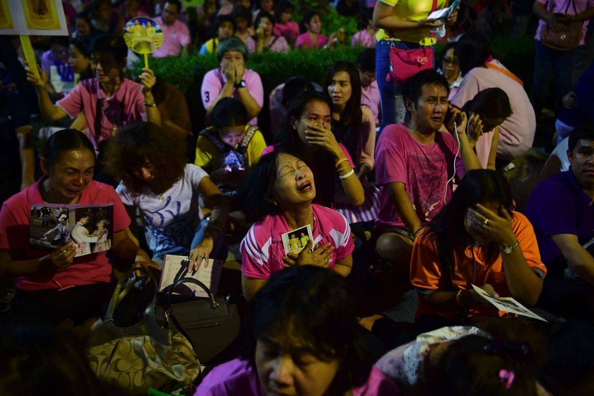 Thai people mourn as they hear the news of the death of King Bhumibol Adulyadej outside Siriraj Hospital in Bangkok.