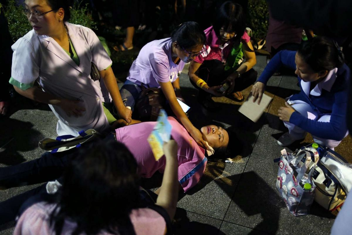 A Thai mourner collapses after hearing of King Bhumibol Adulyadej's death at the Siriraj Hospital in Bangkok.