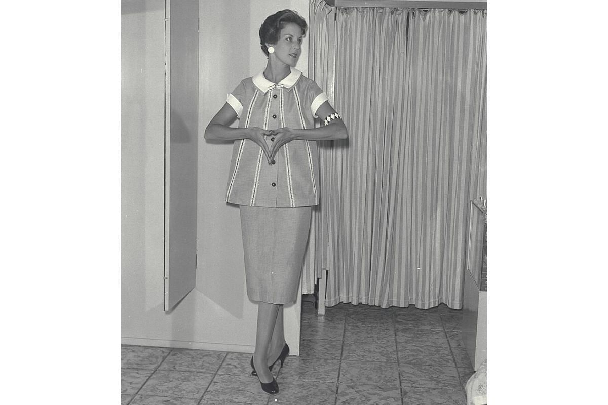 A 1957 photo shows a model wearing a maternity skirt suit, with soft lines of smock-topper plus frills or lace with dressmaker touches and a neckline the centre of attraction.