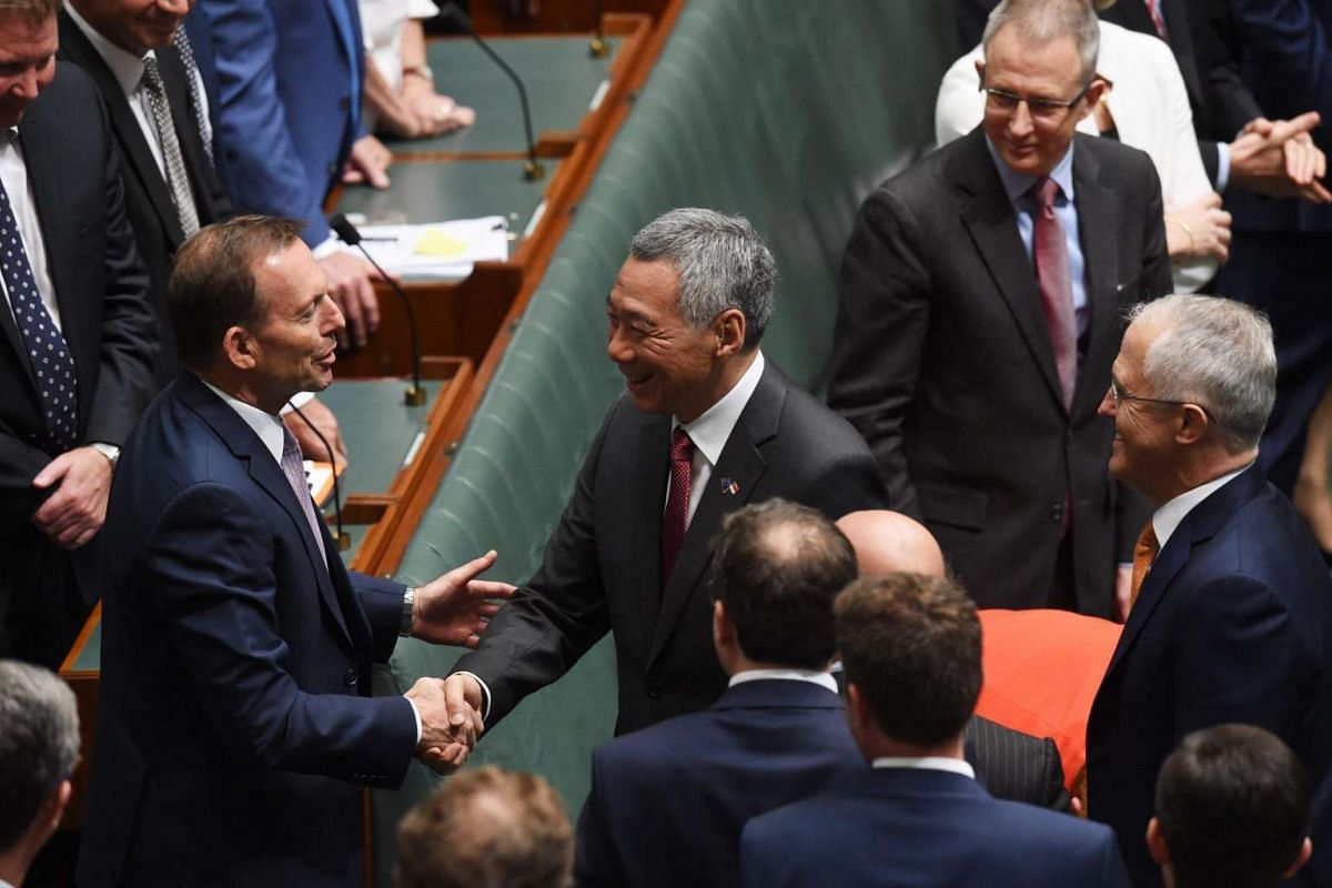 Australia's former Prime Minister Tony Abbott (left) greets Singapore Prime Minister Lee Hsien Loong as current Prime Minister Malcolm Turnbull (right) looks on at a joint sitting of Parliament in the House of Representatives at Parliament House in C