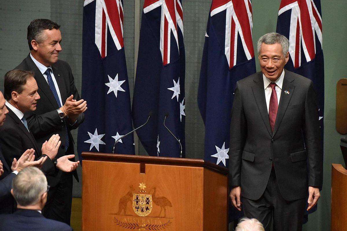 Singapore's Prime Minister Lee Hsien Loong is applauded by members and senators of the Australian government, Parliament House in Canberra on Oct 12, 2016.