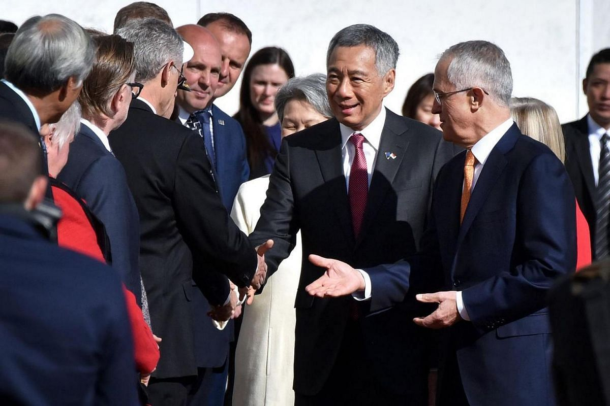 Singapore's Prime Minister Lee Hsien Loong is introduced to members of the Australian Government by Prime Minister Malcolm Turnbull (right) during a ceremonial welcome at Parliament House in Canberra on Oct 12, 2016.