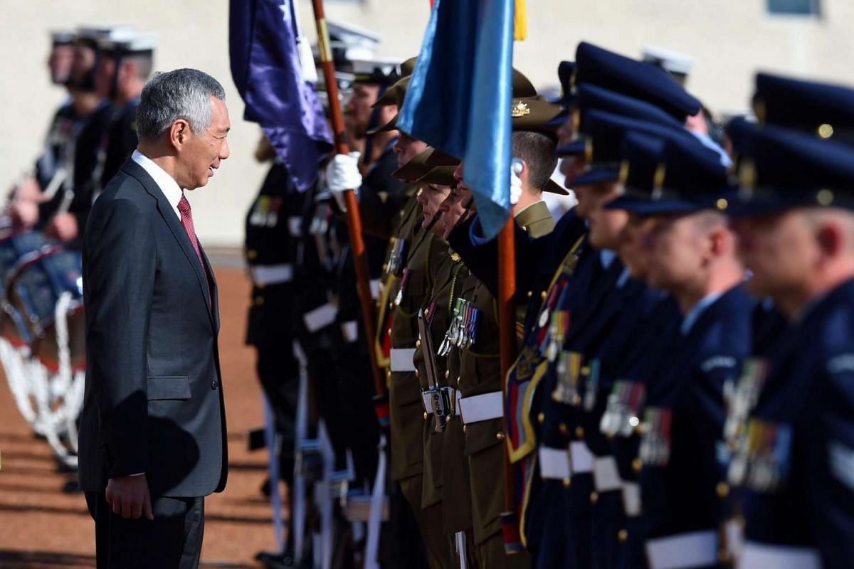 Prime Minister Lee Hsien Loong inspects a guard of honour during a ceremonial welcome at Parliament House in Canberra, Australia, on Oct 12, 2016.