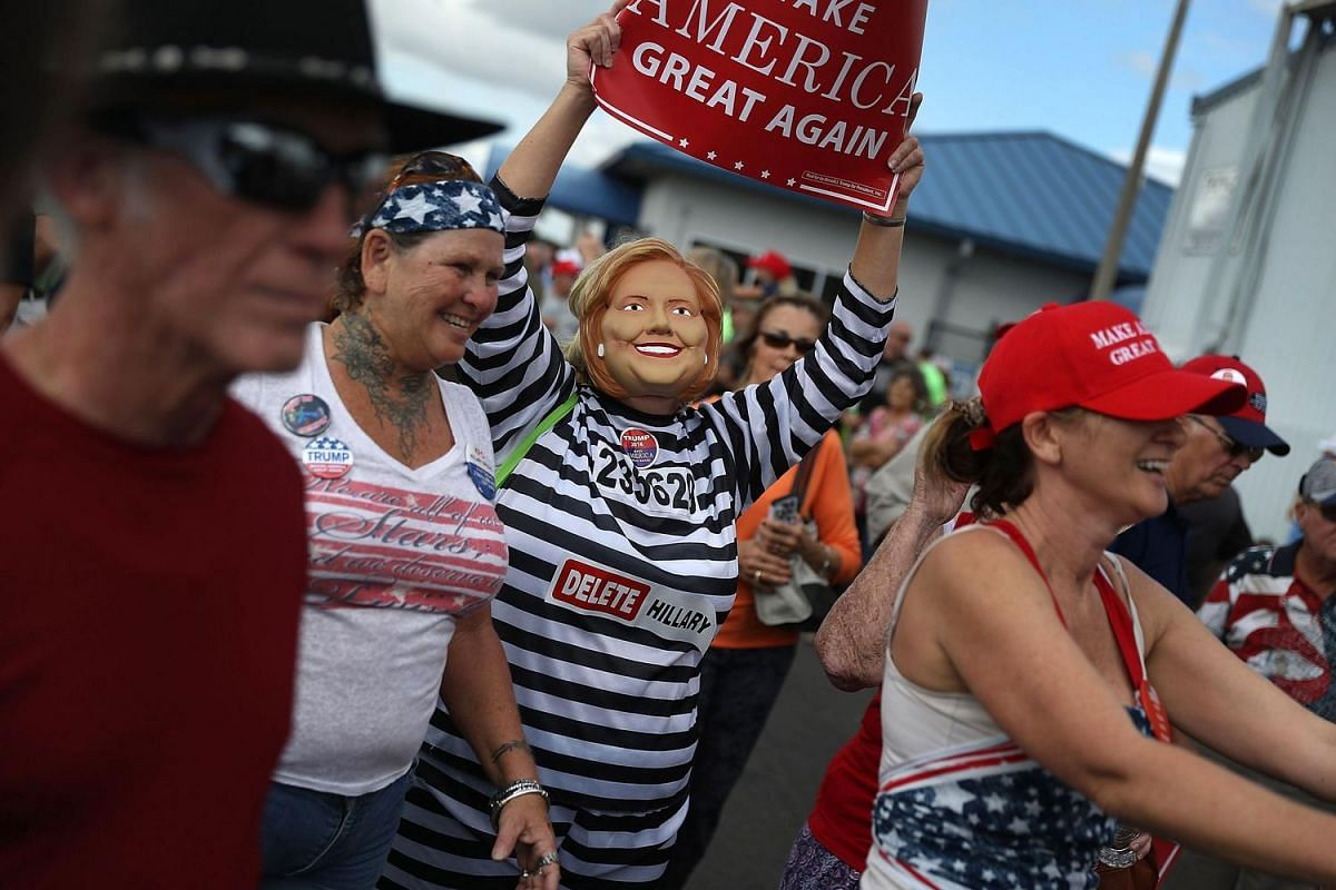 A supporter of Republican presidential candidate Donald Trump wears anti-Hillary Clinton prison garb as people wait for him at his campaign rally at the Lakeland Linder Regional Airport on Oct 12, 2016, in Lakeland, Florida.