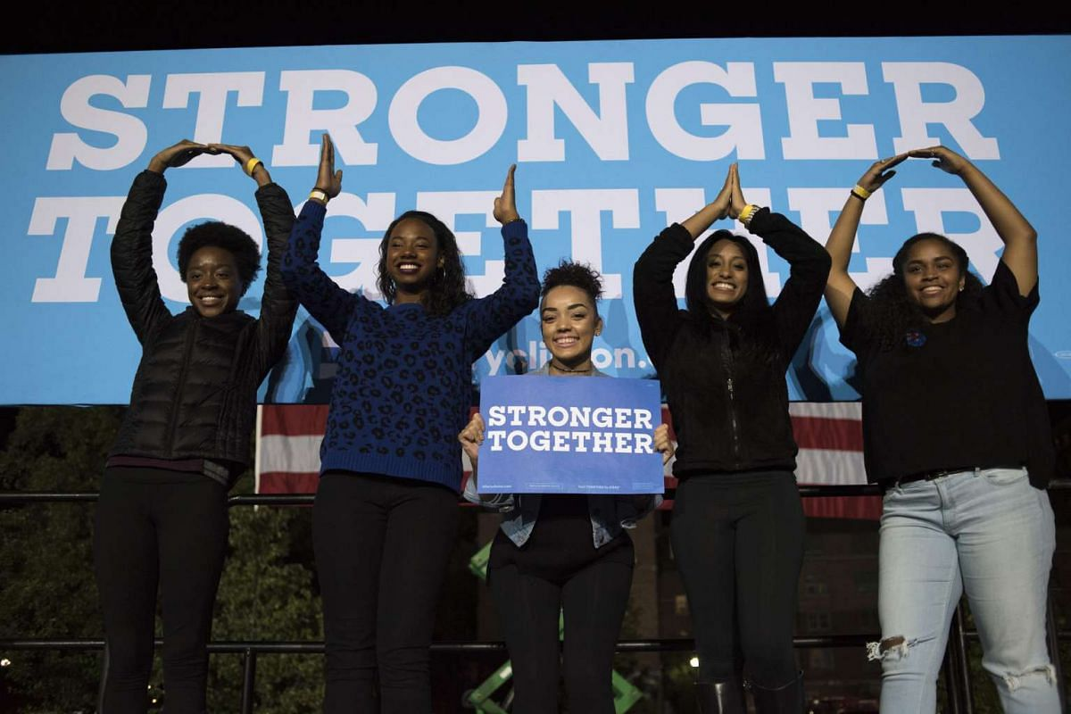 Attendees pose in front of a banner during a campaign event for Hillary Clinton, 2016 Democratic presidential nominee, in Columbus, Ohio, US on Oct 10, 2016.