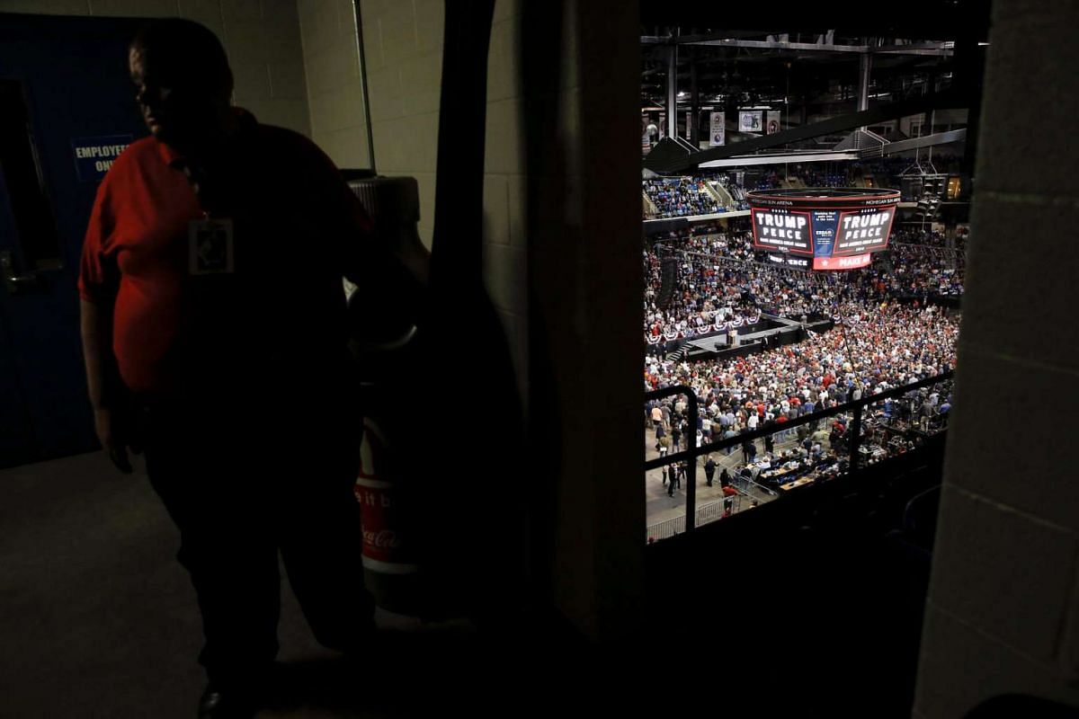 An usher holds open a curtain to a balcony looking down on where Republican US presidential nominee Donald Trump is speaking at a campaign rally in Wilkes-Barre, Pennsylvania, on Oct 10, 2016.