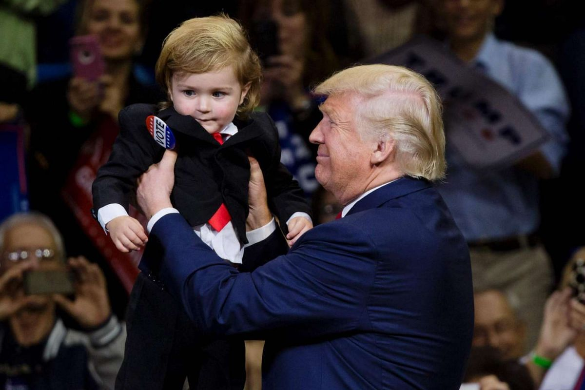 Republican presidential nominee Donald Trump holds as child dressed as him during a rally at Mohegan Sun Arena in Wilkes-Barre, Pennsylvania on Oct 10, 2016.