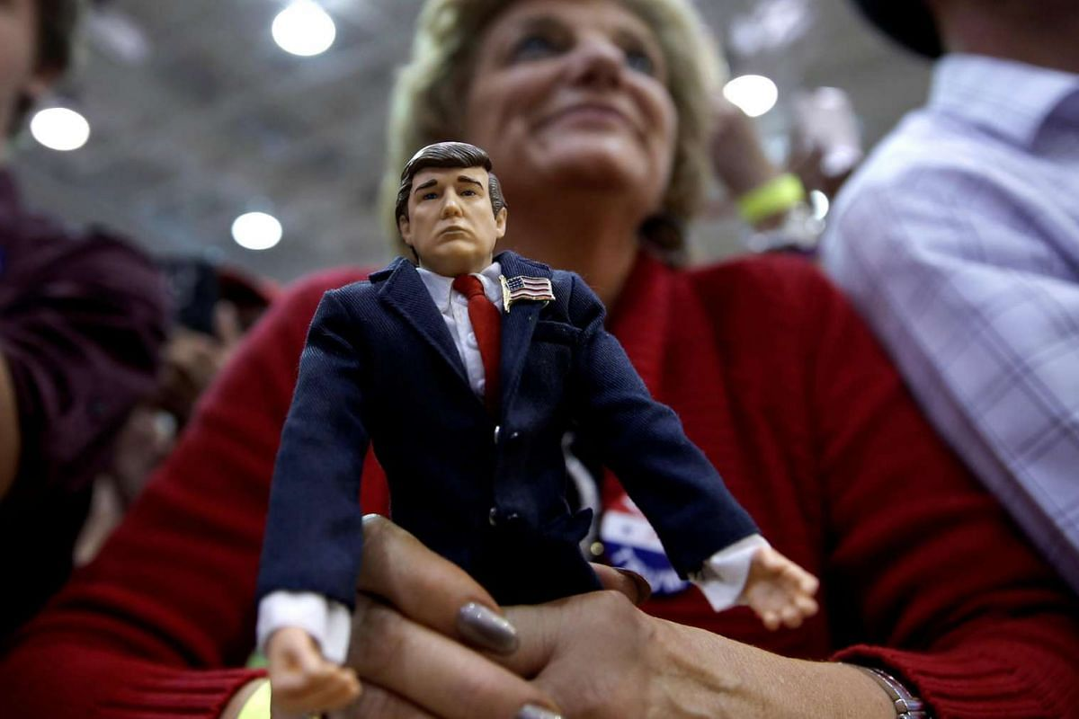 A supporter of Republican US presidential nominee Donald Trump holds a Trump doll as she listens to Trump speak at a campaign rally in Ambridge, Pennsylvania, on Oct 10, 2016.