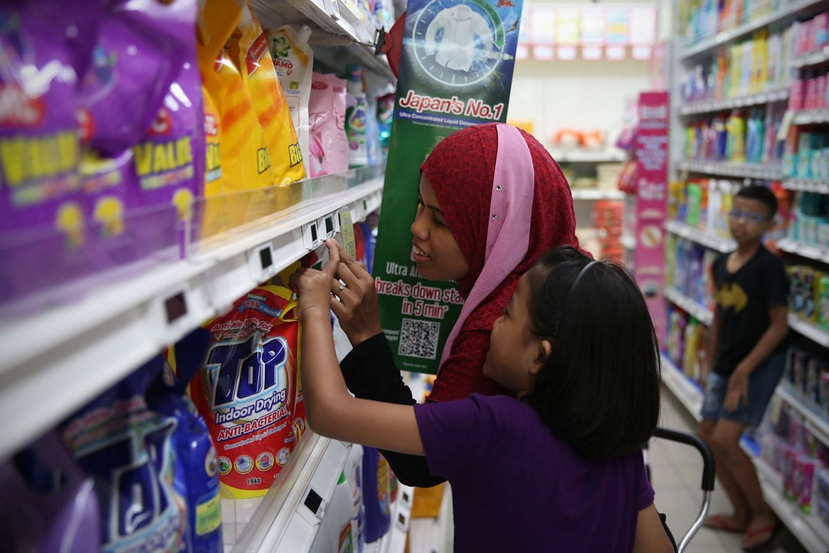 Madam Norrizan getting the help of her 10-year-old daughter, Puteri, as they shop for groceries at a nearby FairPrice supermarket. The labels and price tags have to be extremely close to her eyes for her to make out the information on them.