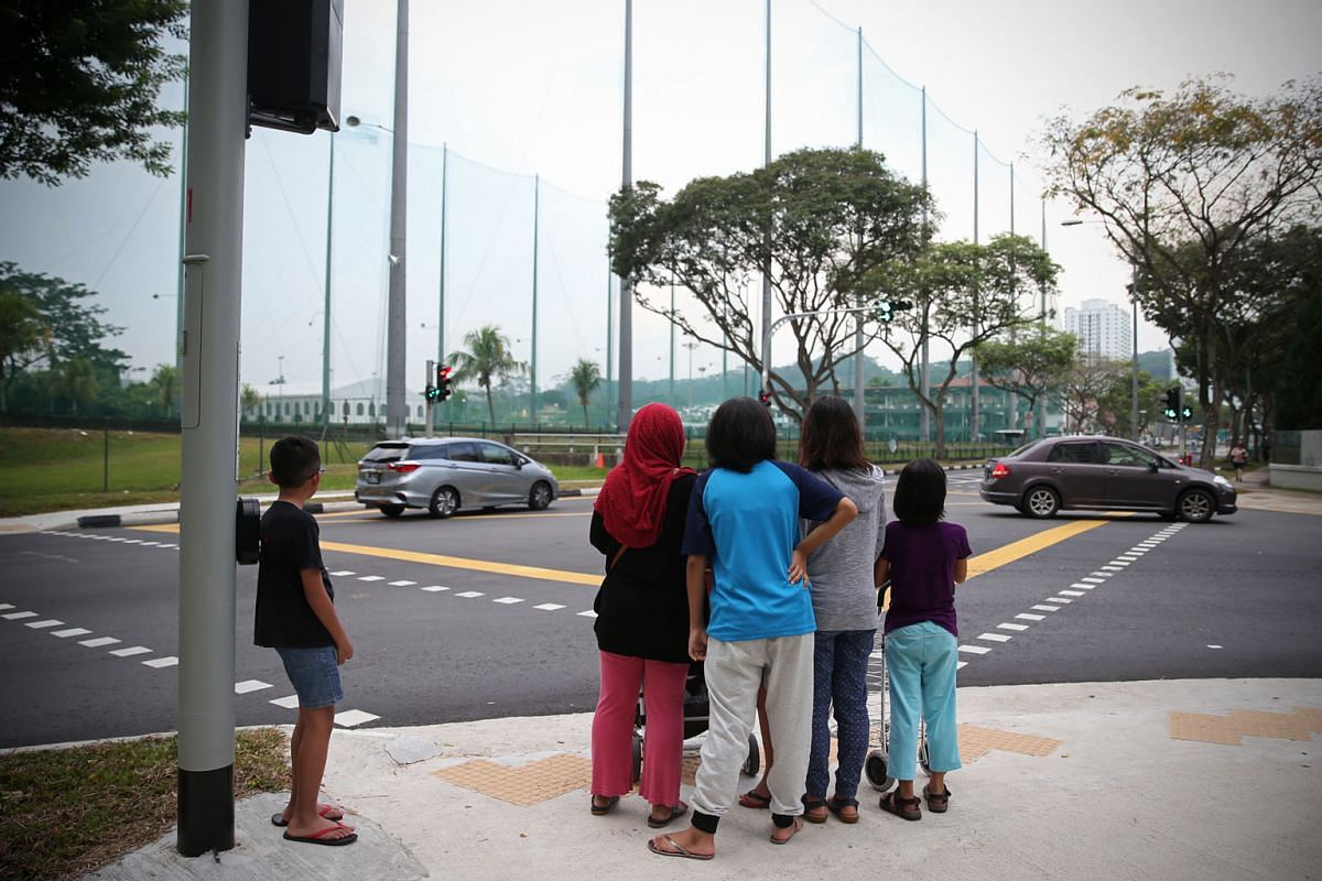 Madam Norrizan standing at the traffic light, which she always uses, as the family goes shopping together. It is not safe for her to go out at night, because she cannot tell where moving vehicles are based on the lights from their headlamps.
