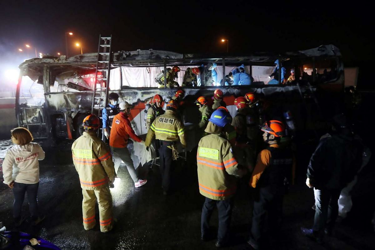 Fire and rescue services at the scene of a bus accident near Ulsan, on South Korea's south-eastern coast on October 14, 2016. At least 10 people were killed and seven others seriously injured when their tour bus caught fire on a highway. PHOTO:  AFP/