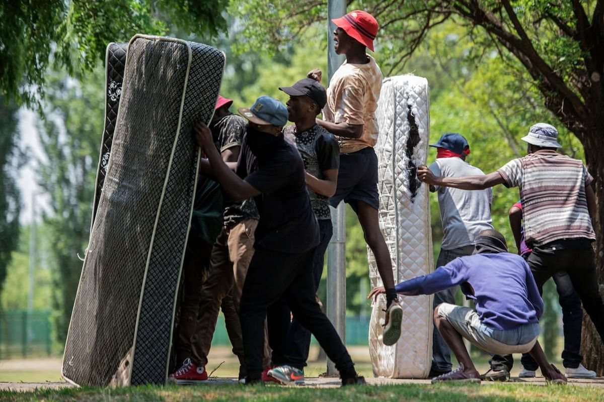 Students from Vaal University of Technology (VUT) take cover behind mattresses during clashes with South African anti-riot police and campus security at a demonstration in support of the Fees Must Fall Movement in Vanderbijlpark on October 13, 2016.