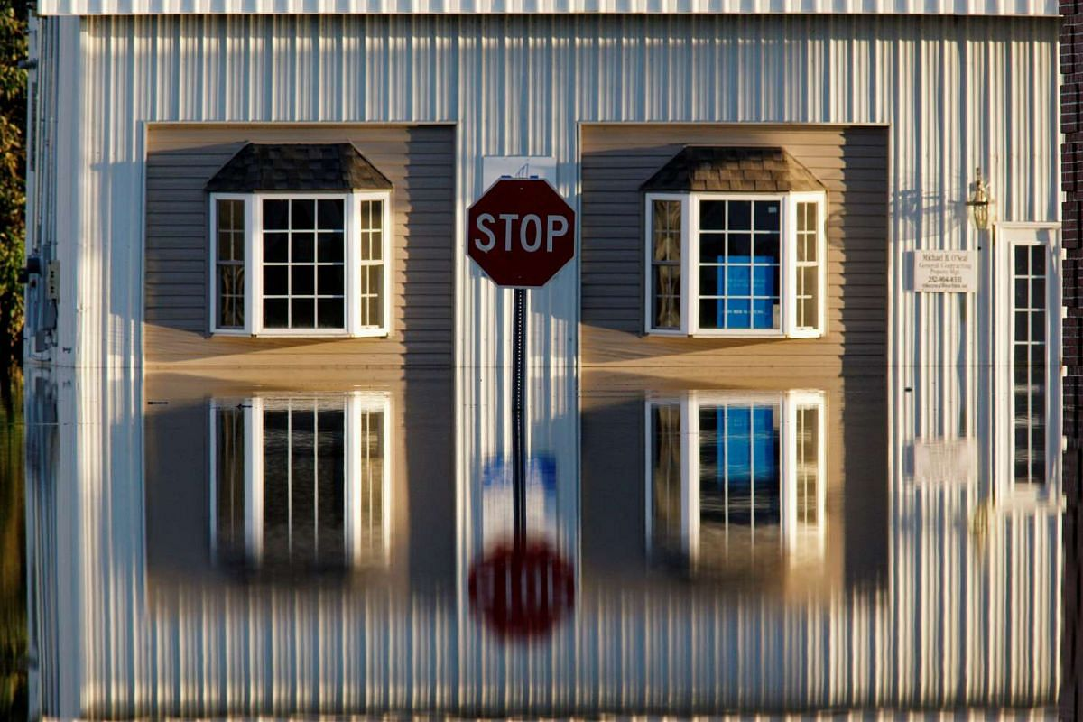 A building and street signs are reflected in flood waters as the Tar River rises to dangerous levels in the aftermath of Hurricane Matthew, in Tarboro, North Carolina on October 13, 2016. PHOTO: REUTERS