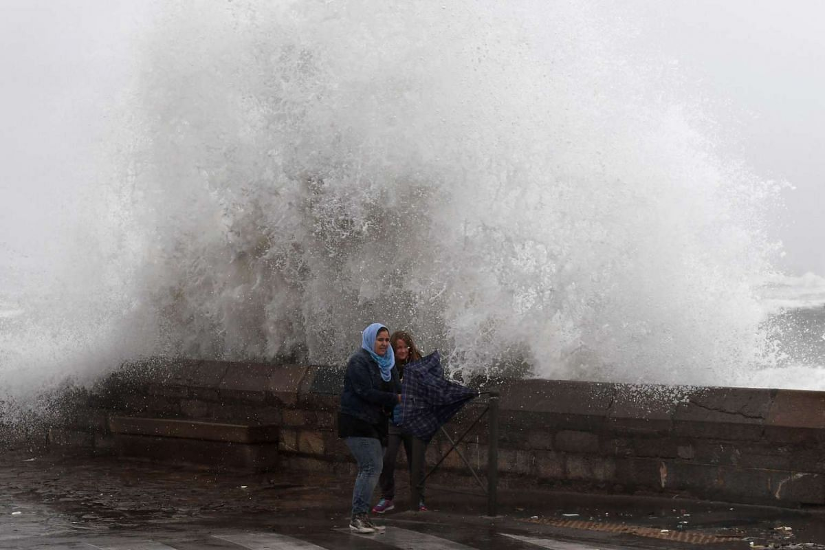 A wave breaks on a cliff street at the port of Sete, southern France, as people walk by with their umbrellas during a storm on October 13, 2016 where the wind blows more than a hundred kilometres per hour. PHOTO: AFP