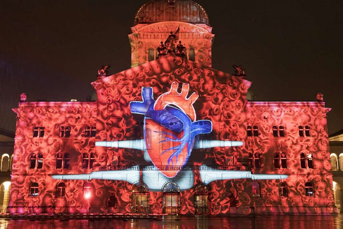 The light spectacle 'Rendez-vous Bundesplatz' projects images on the facade of the federal parliament building in Bern, Switzerland, October 13, 2016. The light show is dedicated to the 150th anniversary of the Swiss Red Cross. PHOTO: EPA