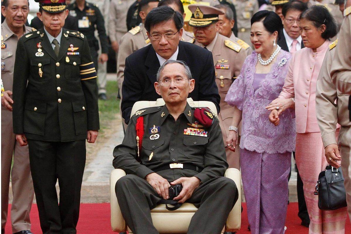 Thai King Bhumibol Adulyadej (centre), Queen Sirikit (second from right) and Princess Maha Chakri Sirindhorn (right) visiting Thung Makham on May 25, 2012.