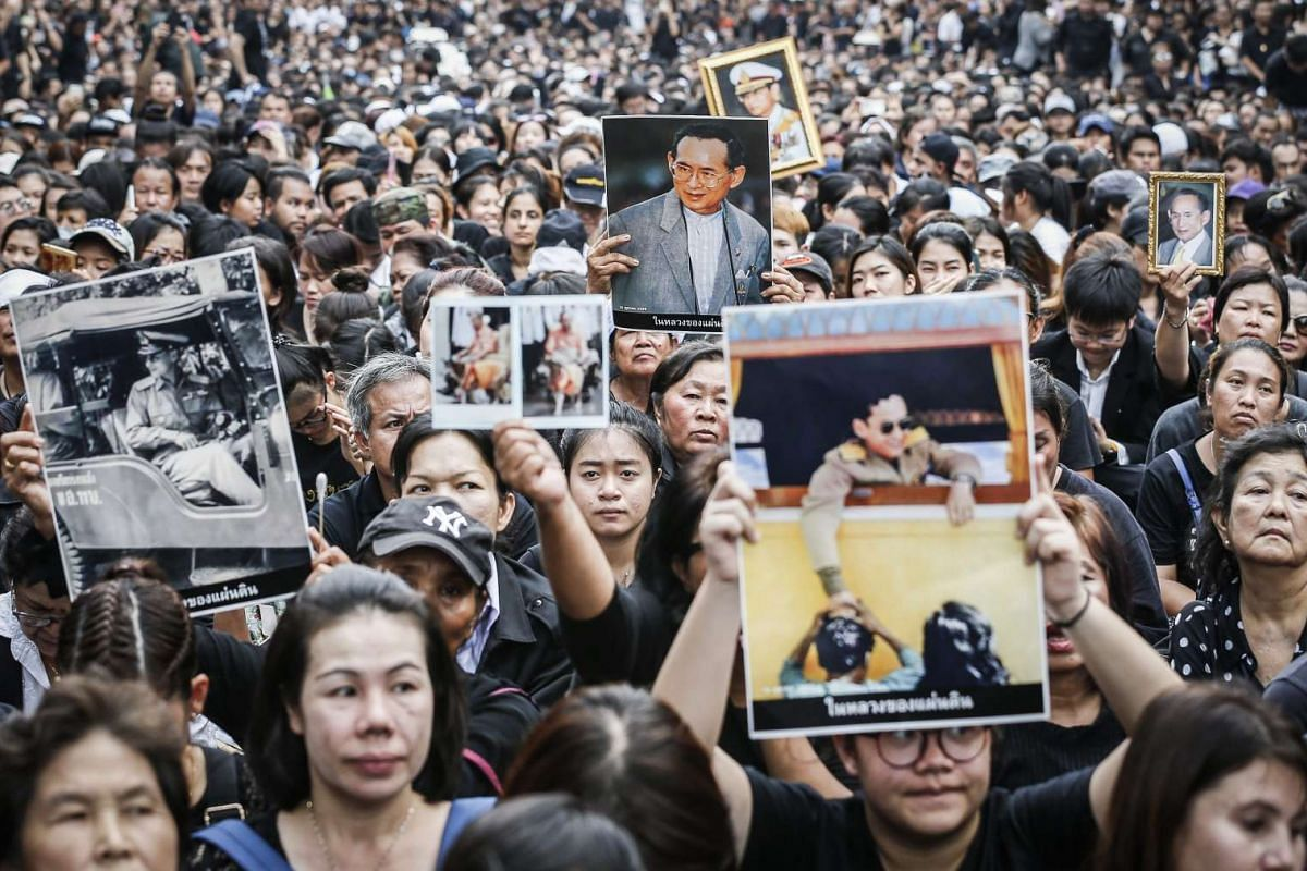 Thais hold pictures of King Bhumibol Adulyadej as they wait for the procession to transport his body from the Siriraj Hospital to the Grand Palace in Bangkok on Oct 14, 2016.