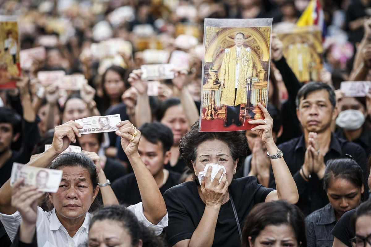 Thais mourn as a convoy of vehicles carrying the body of King Bhumibol Adulyadej moves towards the Grand Palace in Bangkok, Thailand, on Oct 14, 2016.