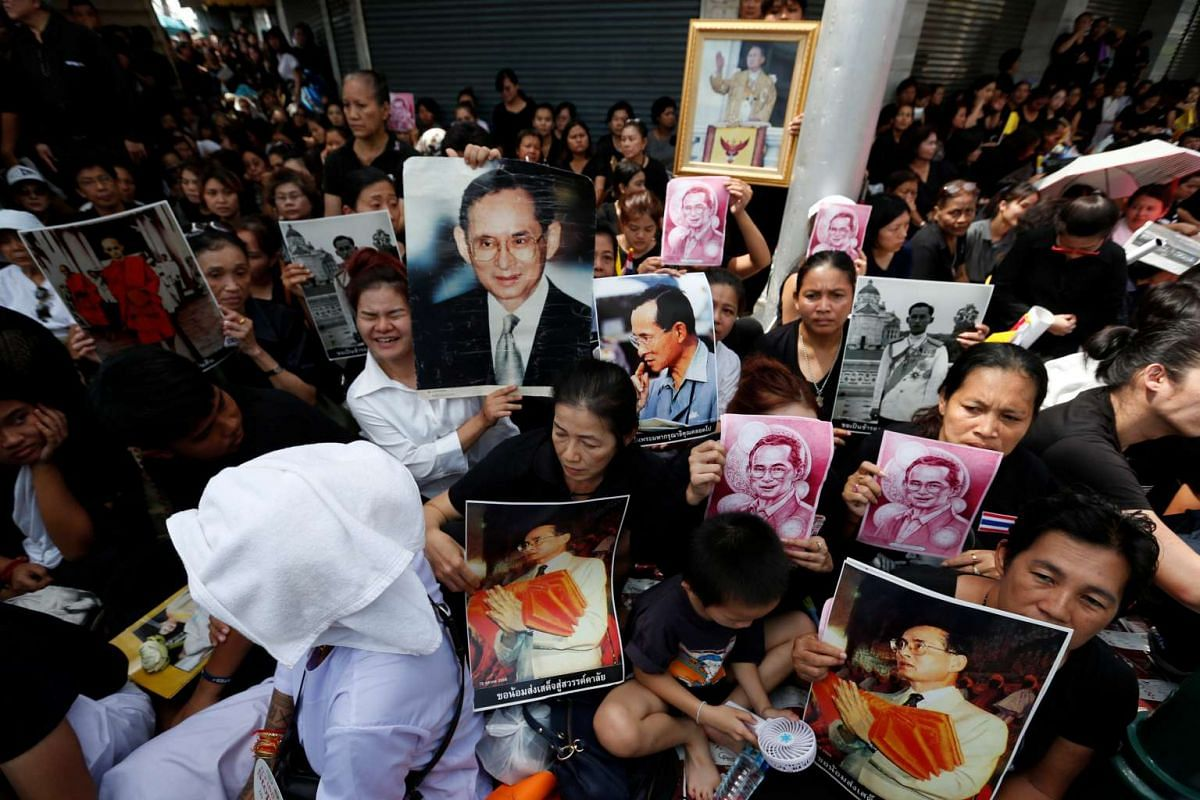 People in Bangkok hold portraits of King Bhumibol Adulyadej as they wait for the royal procession transporting his body to pass by on Oct 14, 2016.