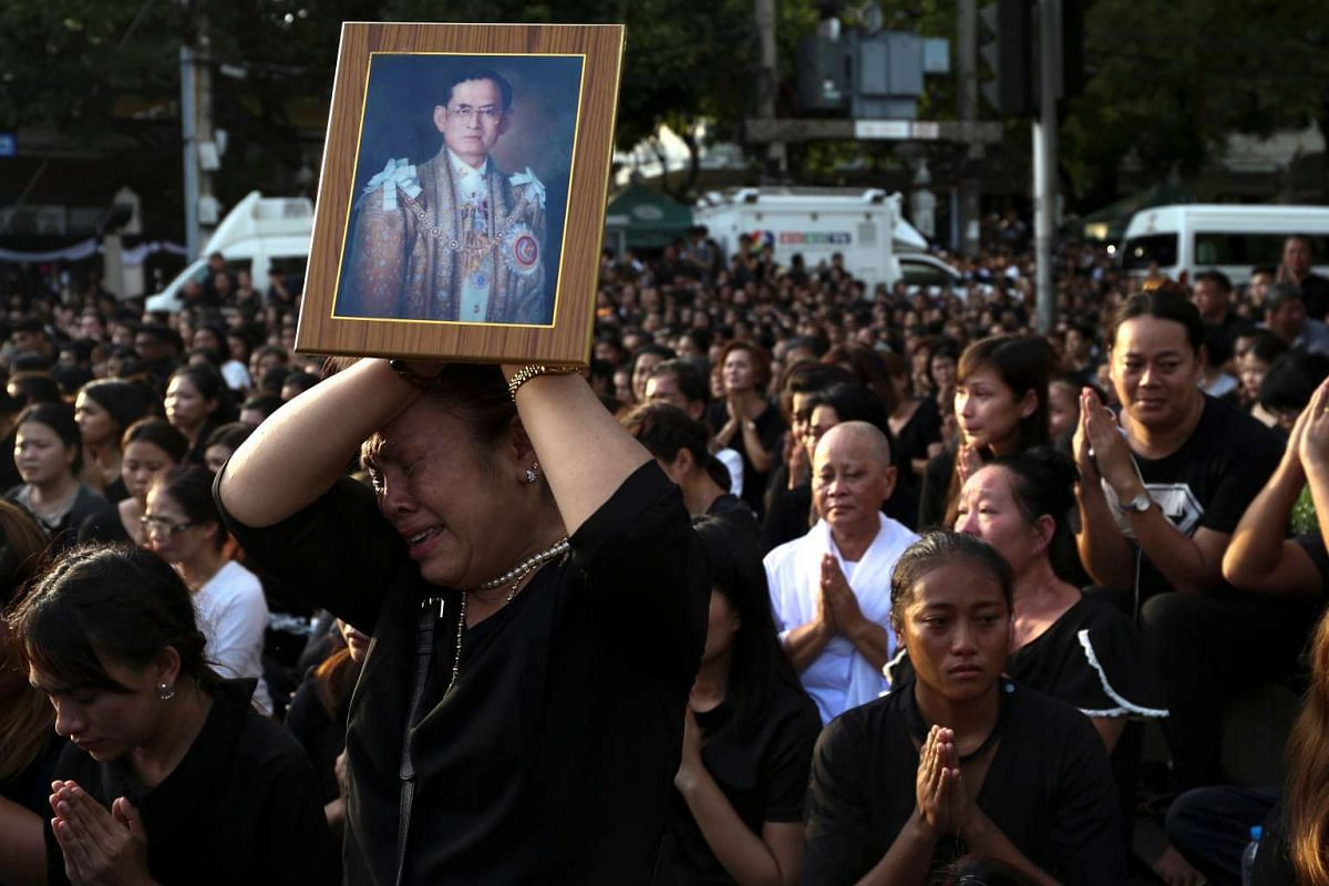 A woman cries while holding up a portrait of King Bhumibol Adulyadej while his body is being transported to the Grand Palace in Bangkok on Oct 14, 2016.