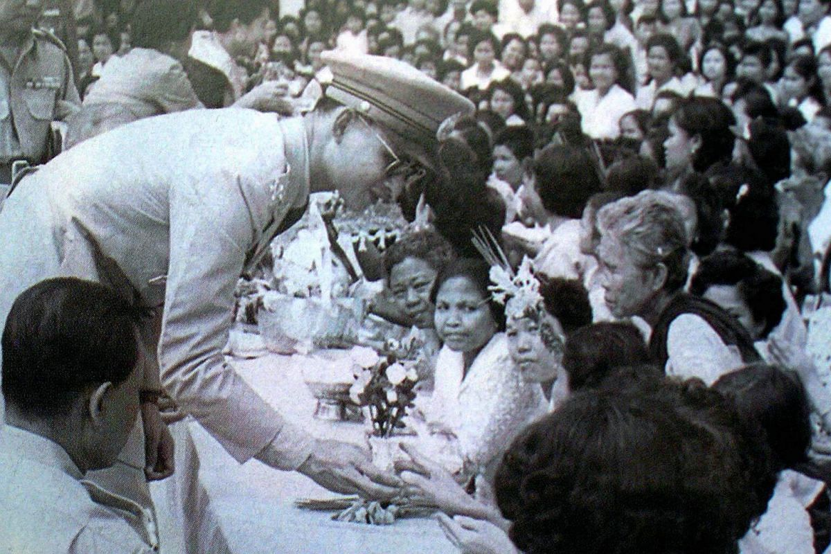 King Bhumibol Adulyadej receiving garlands from villagers in this undated file photo made available by the Thai Royal Bureau on June 5, 2006