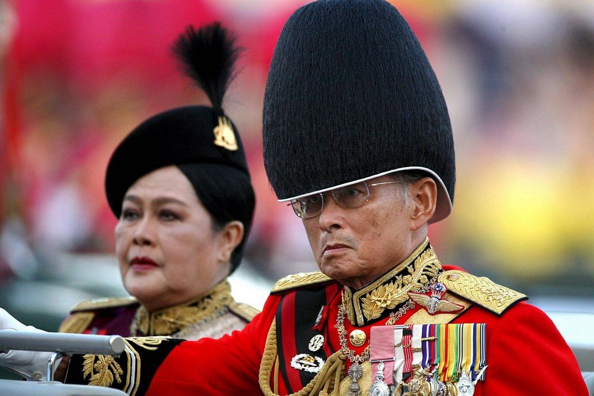 Thai King Bhumibol Adulyadej and his wife Queen Sirikit reviewing the guard of honour during the military parade to celebrate his 81st birthday in Bangkok on Dec 2, 2008.