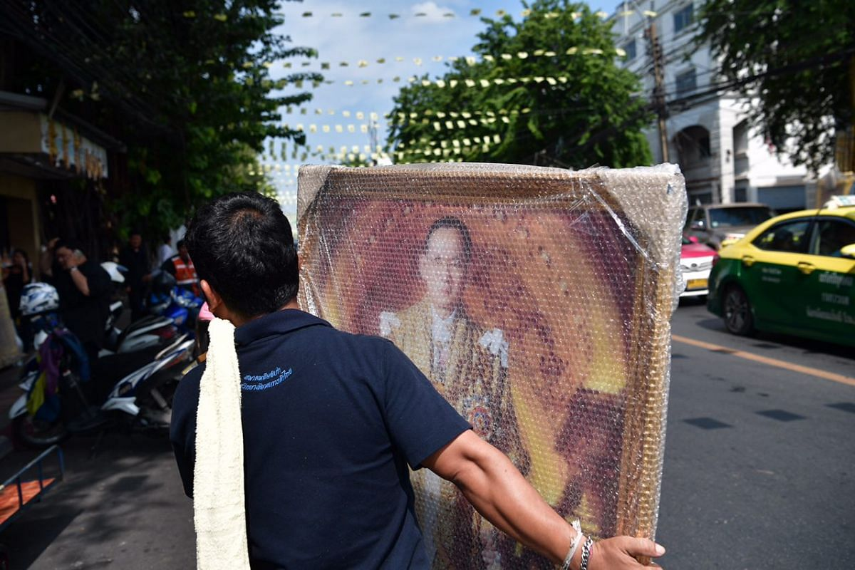 People shop for pictures of Thailand's late King Bhumibol Adulyadej along Dinso Road in Bangkok.