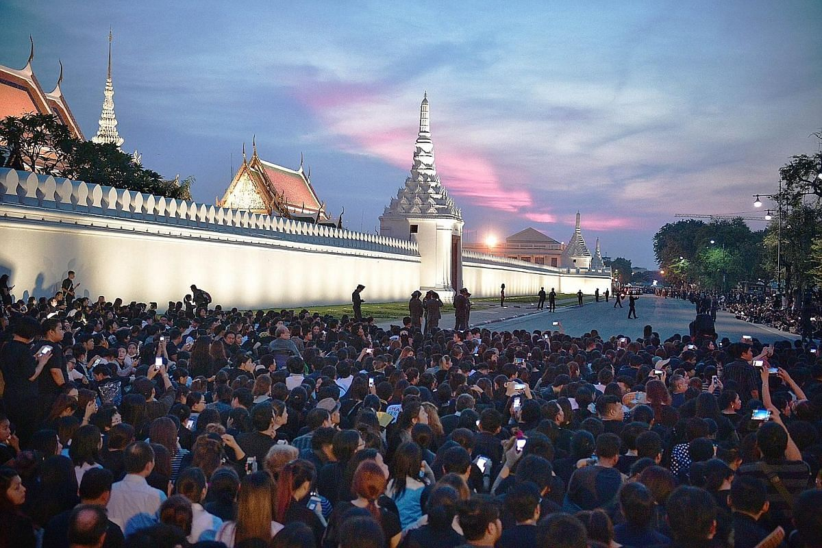 Many hold Thai baht banknotes with pictures of the King as they waited for the procession carrying his body from the Siriraj Hospital to the Grand Palace in Bangkok yesterday. People gathering outside the Wat Phra Kaew within the Grand Palace compoun