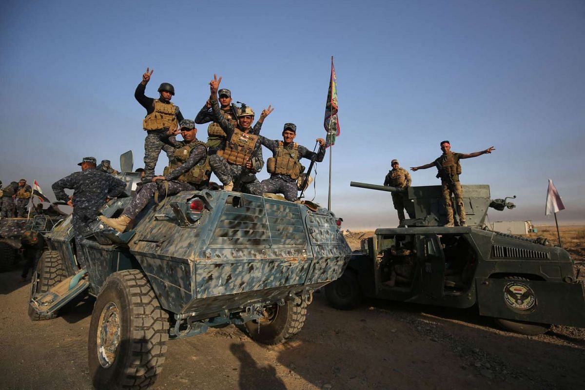 Iraqi forces flash the sign for victory as they deploy in the area of al-Shourah, south of Mosu on Oct 17, 2016.
