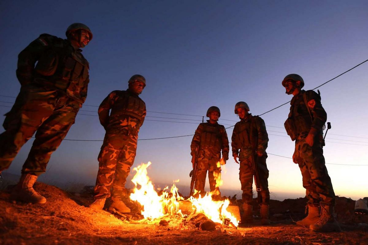 Iraqi Kurdish Peshmerga fighters stand next to a fire as they gather on the top of Mount Zardak, east of Mosul on Oct 17, 2016.