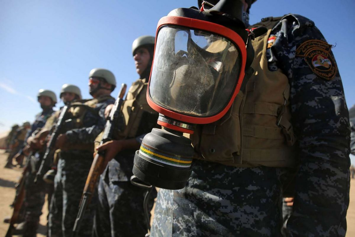 Iraqi policemen stand at attention with gasmasks at the Qayyarah military base, south of Mosul on Oct 17, 2016.