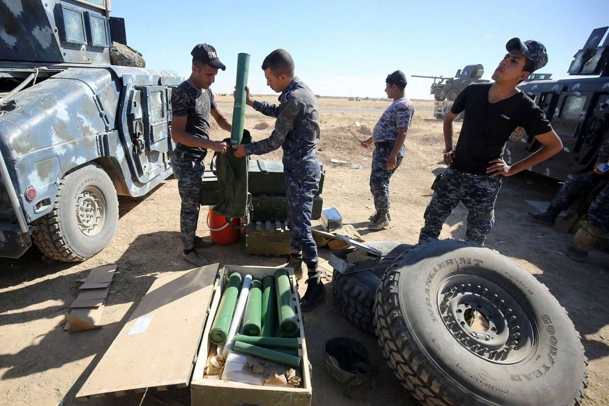 Iraqi policemen inspect their weapons at the Qayyarah military base, south of Mosul on Oct 17, 2016.