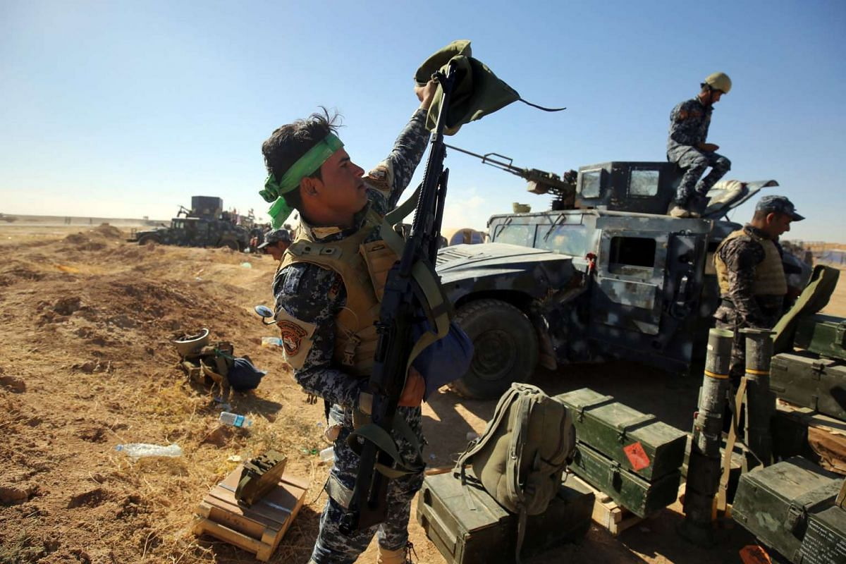 An Iraqi policeman inspects his weapon at the Qayyarah military base, south of Mosul on Oct 17, 2016.