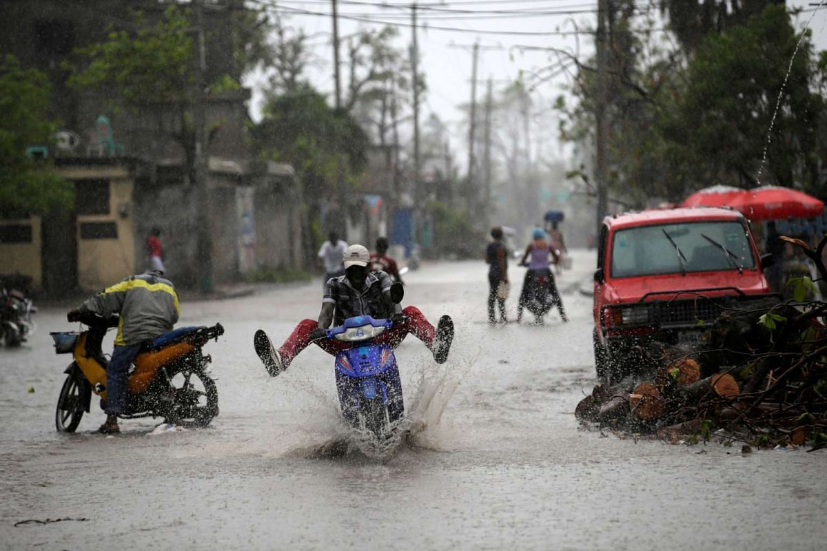 A man riding a motorbike drives on a flooded street during rain after Hurricane Matthew in Les Cayes, Haiti, October 17, 2016. PHOTO: REUTERS