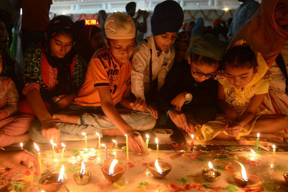 Indian Sikh devotees light candles at the Golden Temple in Amritsar on October 17, 2016 during an event to mark the birth anniversary of the fourth Sikh Guru Ramdas. PHOTO: AFP