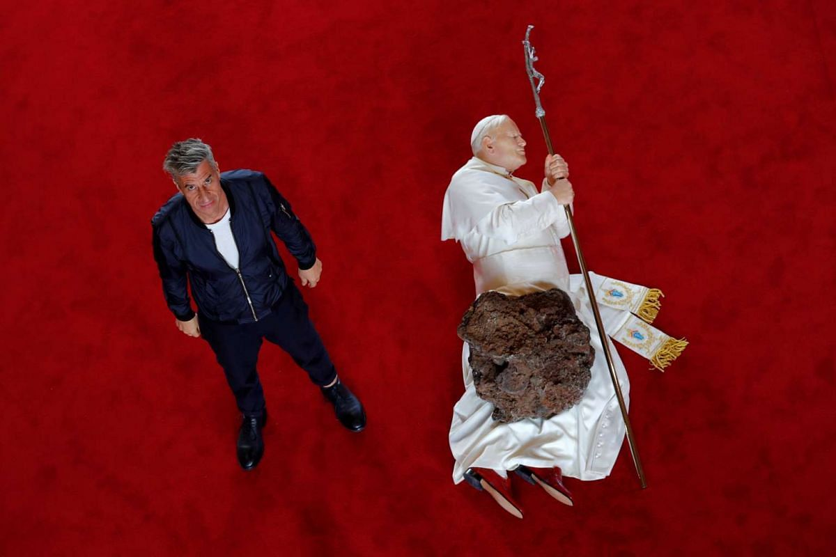 """Italian artist Maurizio Cattelan poses with his creation """"La Nona Ora"""" (The Ninth Hour, 1999) prior to the opening of the exhibition """"Not Afraid of Love"""" at the Hotel de la Monnaie in Paris, France, October 17, 2016. PHOTO: REUTERS"""