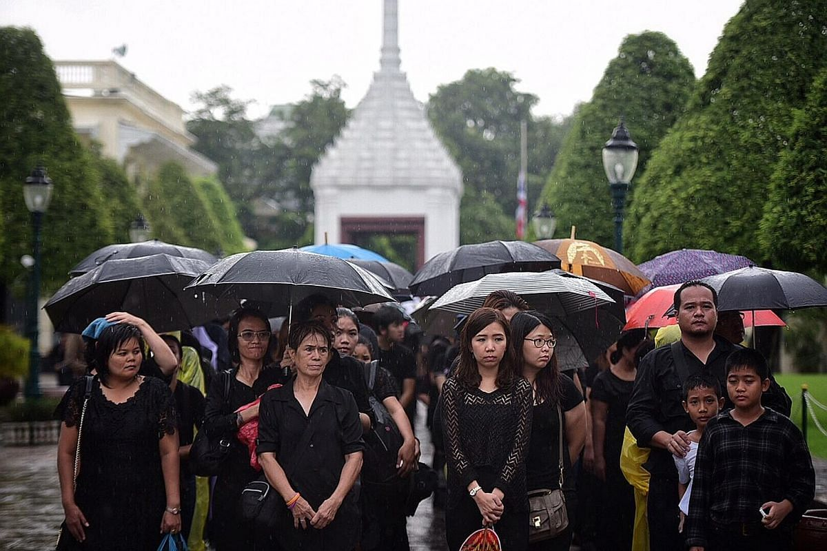 Above: Mourners waiting in the rain to sign the condolence book inside the Grand Palace on Sunday. Prayer rituals continue to be held for King Bhumibol at the palace, while tributes have been put up around the city - on walls and buildings, in homes