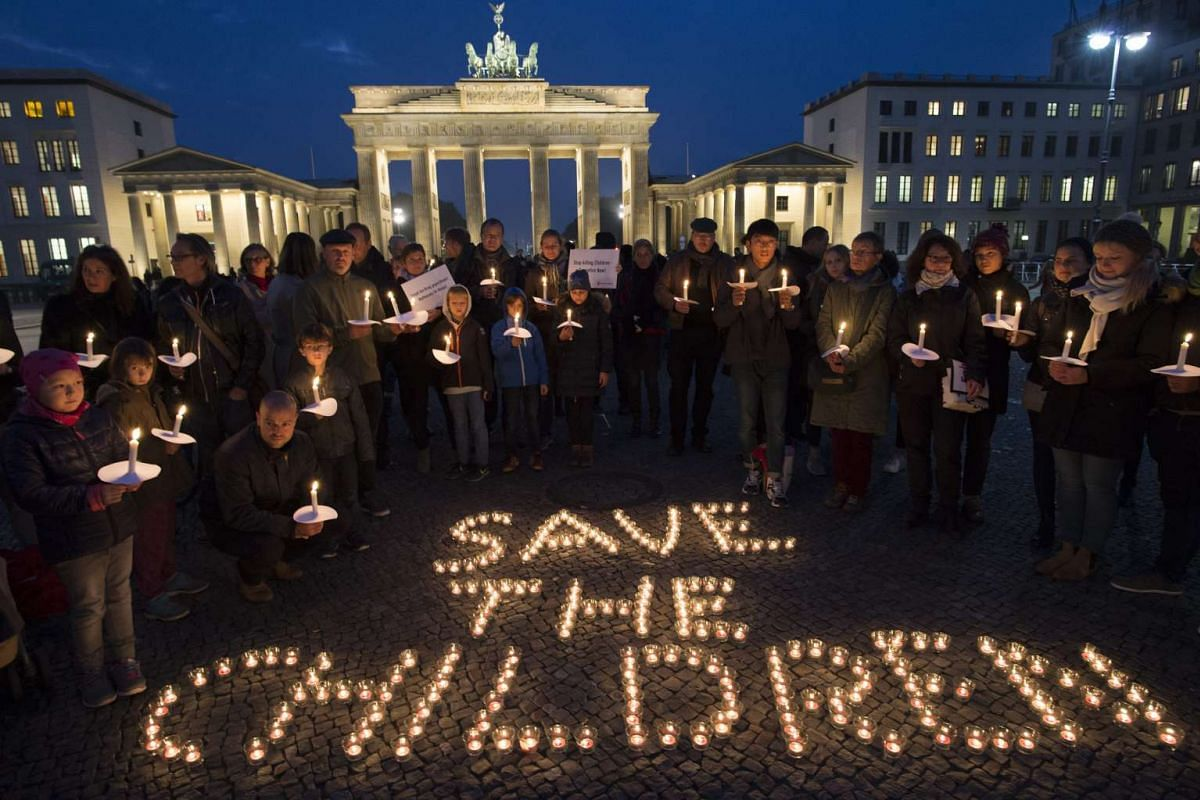 'Save the Children' written out in candles in front of the Brandeburg Gate in Berlin, Germany, on Oct 18, 2016. The international non-governmental organisation (NGO) Save the Children organised a candlelight vigil to commemorate the children who have