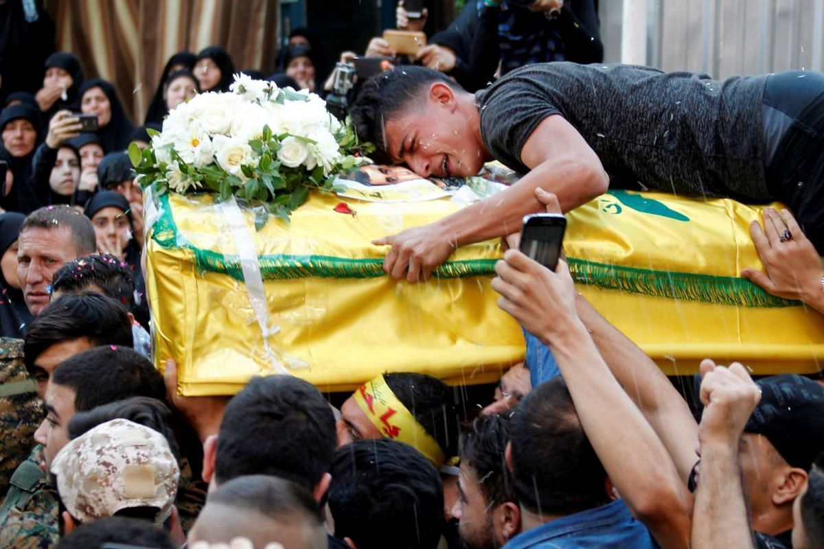 A man reacts while clutching the coffin of Hezbollah fighter Jalal al-Effie, who was killed during clashes in Syria's Aleppo, during his funeral in Beirut's southern suburbs, Lebanon October 18, 2016. PHOTO: REUTERS