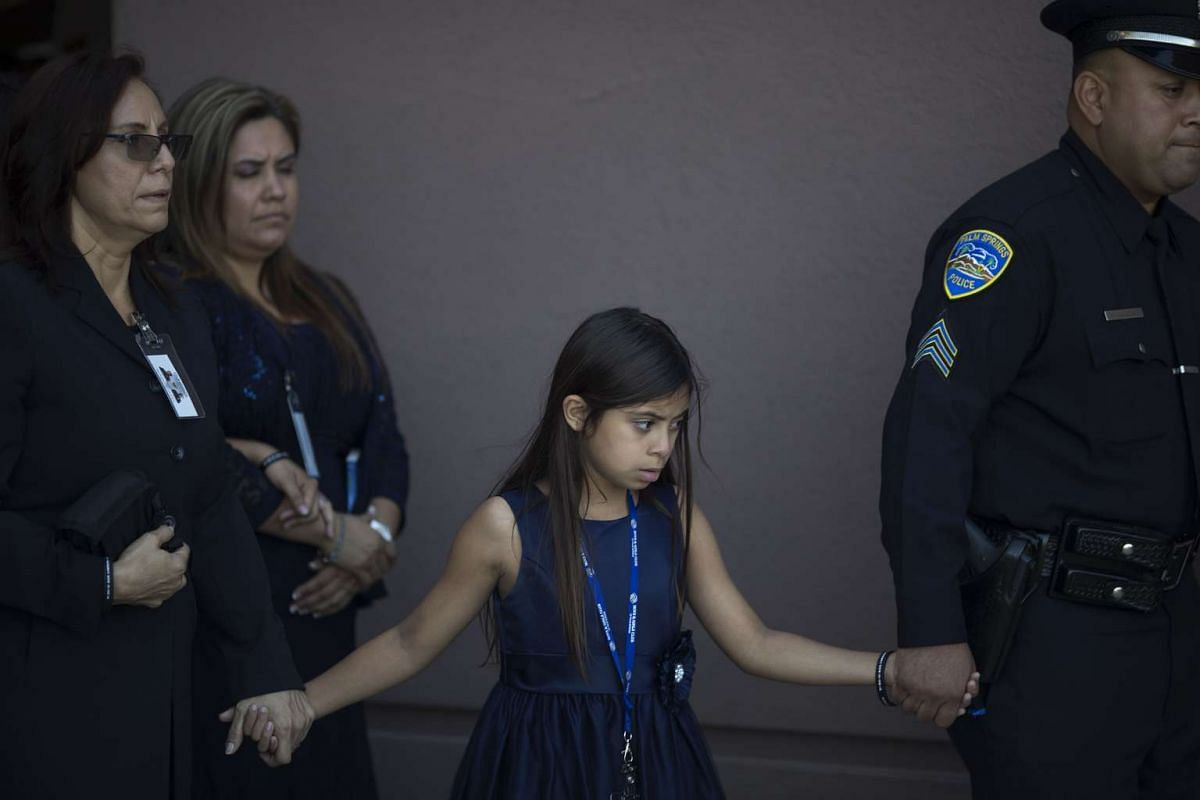 Family members follow the casket carrying the body of officer Jose Gilbert Vega after a funeral service for fallen Palm Springs Police officers Jose Gilbert Vega and Lesley Zerebny at the Palm Springs Convention Center on October 18, 2016 in Palm Spr
