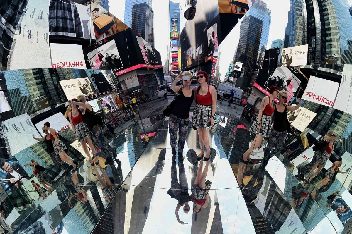 """Tourists walk through a three mirrored surface, a floor and two angled walls, interactive installation by Cuban artist Rachel Valdés Camejo titled """"The Beginning of the End"""" in Times Square in New York October 19, 2016. PHOTO: AFP"""